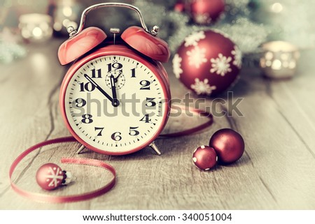 """""""Happy New Year!"""" Greeting card with alarm clock showing five to twelve and winter arrangement. This image is toned. Focus on the clock. - stock photo"""