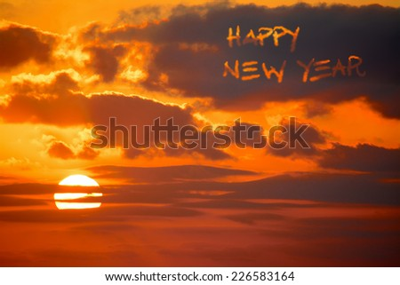 """happy new year"" written in the sky at sunset - stock photo"
