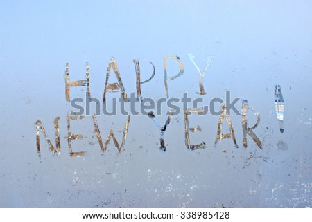 """happy new year"" -  written on frosty winter window background - stock photo"