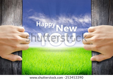 """Happy New You"" Motivational quotes. Hands opening a wooden door then found a texts floating among new world as green grass field, Blue sky and the Sunrise. - stock photo"