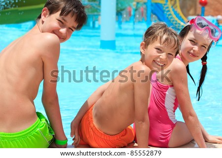 Happy siblings by pool - stock photo