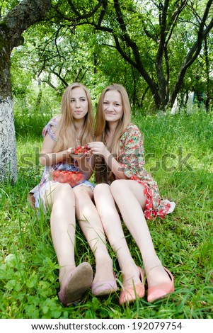 2 happy smiling and looking at camera blond women, sisters or teenage girl friends eating strawberry on summer green garden outdoors background  - stock photo