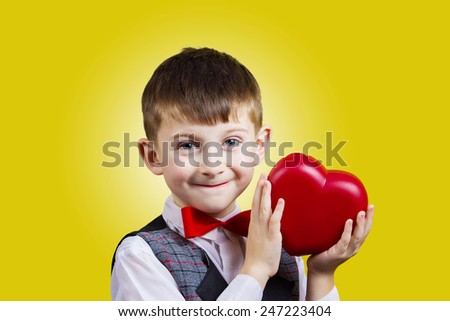 Happy, smiling little boy holding Red heart isolated on yellow background.Concept Love,Care,Health.Facial expression. - stock photo