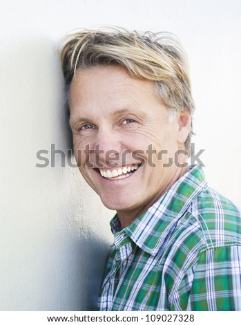happy smiling mature man in forties with blond hair and blue eyes leaning against a white wall.