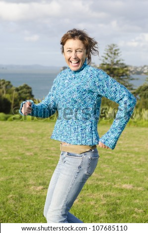 happy smiling mature woman having fun in park running and laughing - stock photo