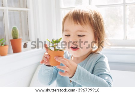 Happy toddler girl playing with little potted plants in her house - stock photo