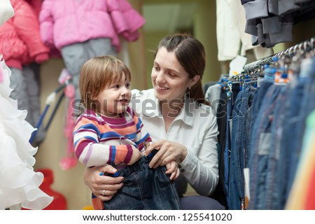 Happy woman and child chooses jeans at shop - stock photo