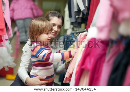 Happy woman and child chooses wear at shop. Focus on girl - stock photo