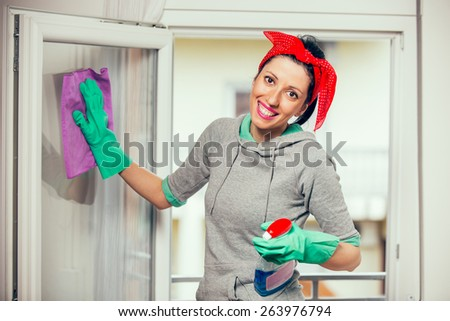Happy woman in gloves cleaning window with rag and cleanser spray at home - stock photo
