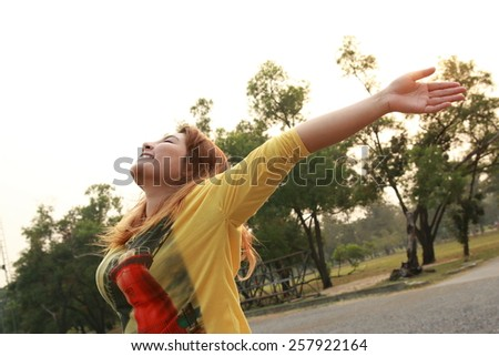 happy woman raises up arms to the sky. Feeling freedom and fresh in garden - stock photo