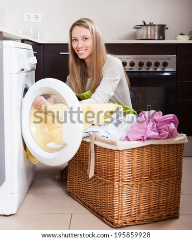 Happy woman with linen basket near washing machine  at home