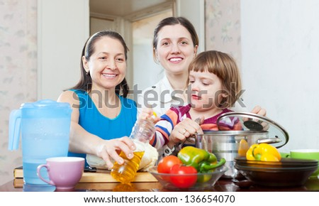 happy women with child cook vegetables in kitchen