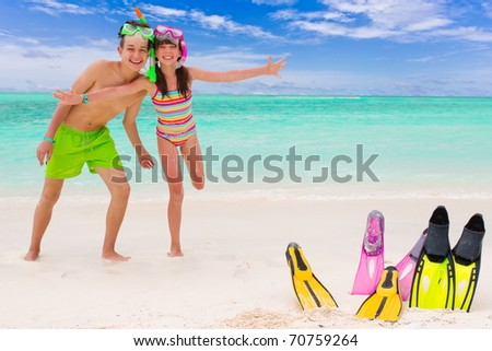 Happy young brother and sister playing in tropical beach with snorkels, flippers embedded in sand.
