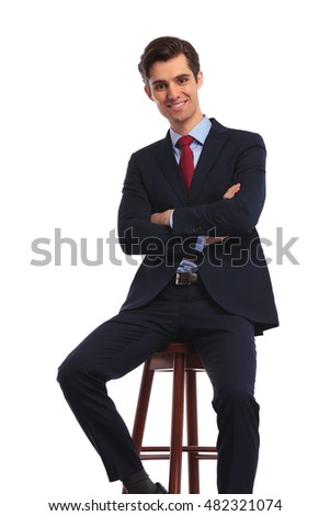 happy young business man with hands crossed sitting on a chair on white background