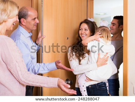 happy young family with two daughters visiting grand parents