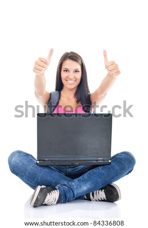 happy young female sitting on floor using laptop, hands raised with thumbs up