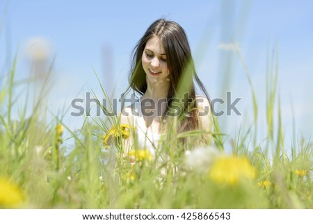 happy young woman picking dandelions on flower meadow