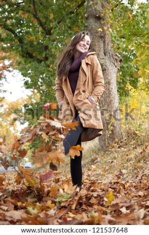 happy young woman walks in autumn leaves