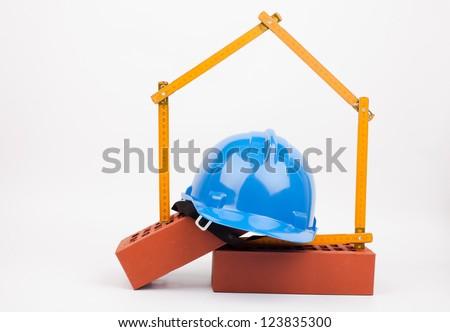 hardhat, bricks and home symbol - stock photo