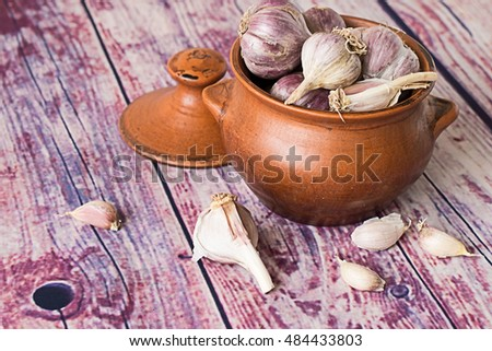 Heads of garlic in a clay pot and garlic cloves on an old wooden table. Selective focus.