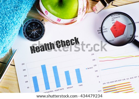 """Health Check"" black text on paper with magnifying glass on red spider bar on wooden table with compass, pen, towel, green apple with measurement tape, and whistles - fitness, diet and healthy concept - stock photo"