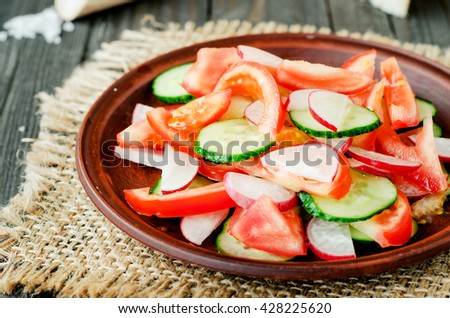 healthy salad with fresh ripe summer vegetables , tomato, cucumber , radishes , spices and white toast on a wooden background - stock photo