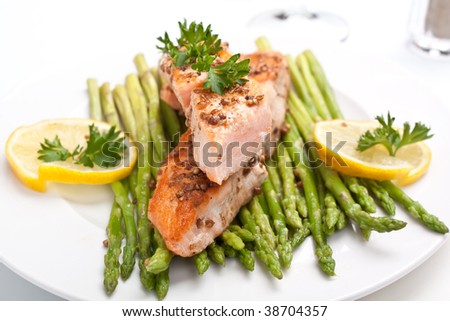 healthy salmon with coriander garnished with asparagus on white plate - stock photo