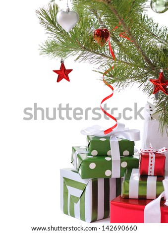 heap of  gift boxes  ornated with satin bow  under decorated Christmas tree - stock photo