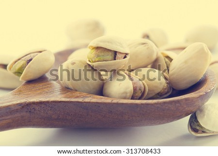 heap salted pistachio nuts on wooden spoon background