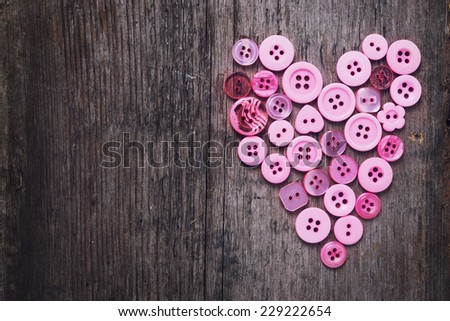 Heart from pink buttons on aged wooden background. Selective focus, horizontal. - stock photo