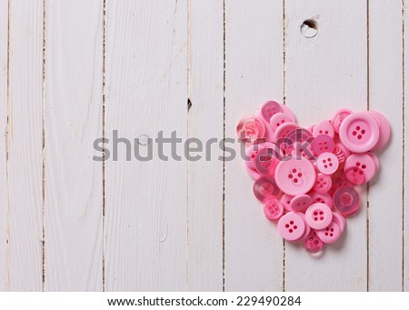 Heart from pink buttons on background from white wooden painted planks. Valentine day background. - stock photo