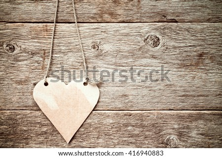 Heart made of paper hanging on wooden background.Copy-space.