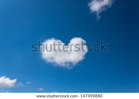 Heart shaped cloud in the blue sky background. - stock photo