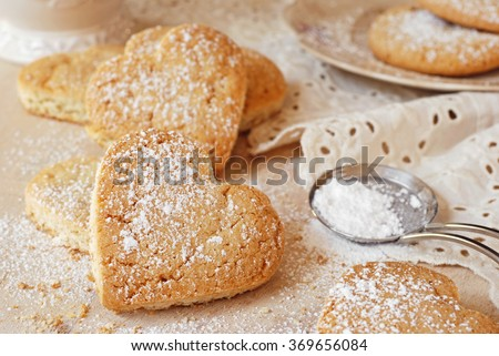 Heart shaped sugar cookies with powdered sugar duster and antique lace. (cookies cut into heart shapes after baking)  Closeup with shallow dof. - stock photo