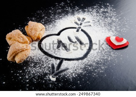 14. Heart with arrow on the flour on the black table. Cookies and red heart. - stock photo