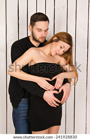 2 hearts formed with hands on the belly of a pregnant woman with twins. handsome man with his beautiful pregnant woman. man and woman looking at a big tummy - stock photo
