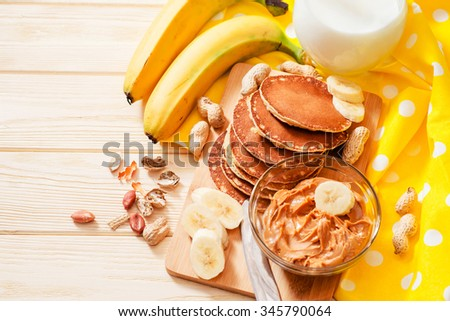 hearty and healthy breakfast , American pancakes with bananas , nuts , peanut butter and milk on a wooden background - stock photo