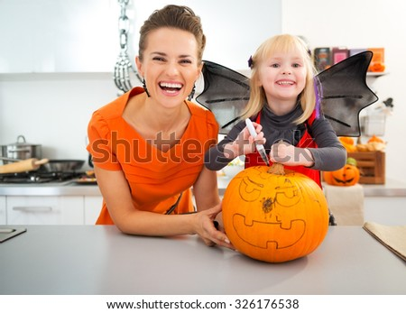 Ð¡heerful mother with halloween dressed daughter creating big orange pumpkin Jack-O-Lantern in decorated kitchen. Traditional autumn holiday - stock photo