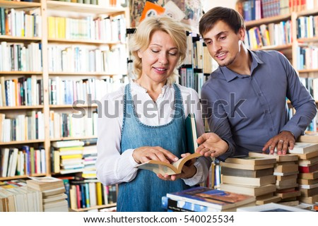 �¡heerful young man and mature woman holding books in hands in book store