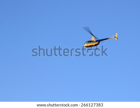 helicopter yellow against the blue sky