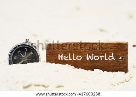 """Hello World"" text on wooden keychain with compass on the tropical white sand beach - vacation and business concept - stock photo"