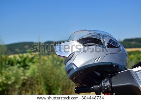 Helmet on a motorcycle mirror (scooter) Natural blurred background landscape - stock photo