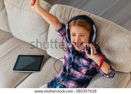 Her favorite song. High angle view of cheerful little girl in headphones gesturing and keeping eyes closed while sitting on the couch at home  - stock photo