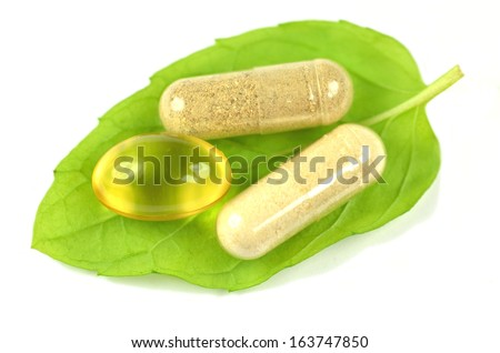 herbal capsules and fish oil capsule on mint leaf isolated on white background
