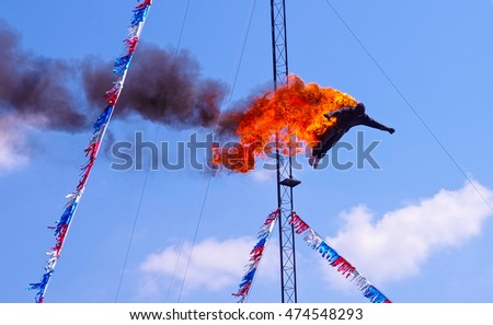 High diver performing a fire dive off a platform above a pool at a circus fair show.  Stuntman dressed in black fire protective suite.  A very dangerous yet exciting athletic sport stunt.