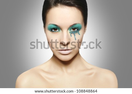 High fashion look.glamour closeup portrait of sexy beautiful brunette woman with black eyes and blue bright colorful makeup caucasian young female with perfect clean skin. Gray background - stock photo