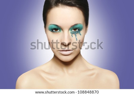 High fashion look.glamour closeup portrait of sexy beautiful brunette woman with black eyes and blue bright colorful makeup caucasian young female with perfect clean skin. purple background - stock photo