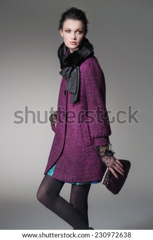 High fashion model in autumn/winter clothes holding purse posing  - stock photo