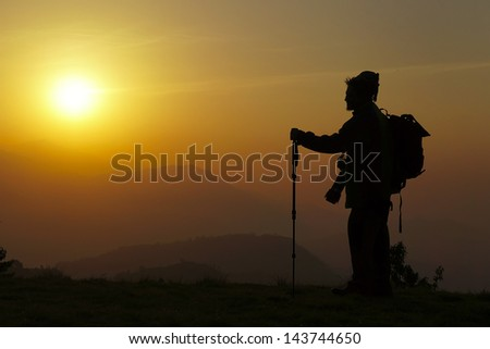 Hiker on top, silhouetted in high mountains  at sunrise - stock photo