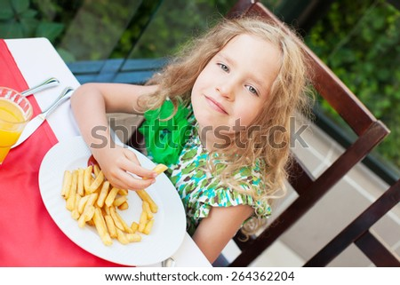 �¡hild eating potato chips in the cafe. Fast food.